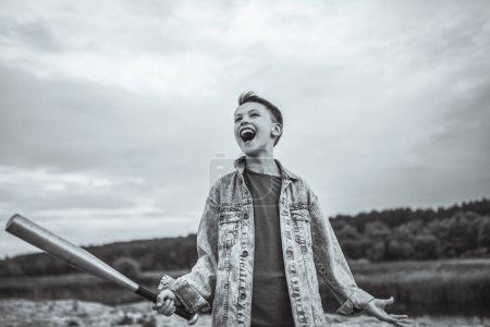 low angle view of excited boy in denim jacket holding baseball bat outdoors, black and white photo