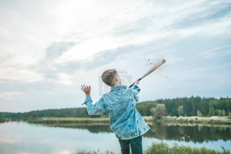 back view of boy in denim jacket playing with baseball bat outdoors