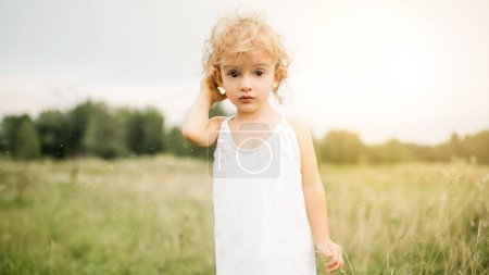 Photo for Adorable child with curly hair standing in field and looking at camera during sunset - Royalty Free Image