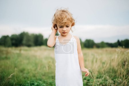 adorable child with curly hair standing in field and looking down