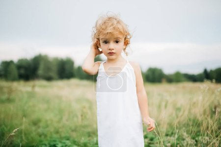 adorable child with curly hair standing in field and looking at camera