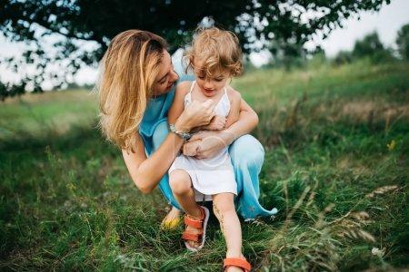 Photo pour Mère accroupi et câlin fille dans le champ près de la forêt - image libre de droit