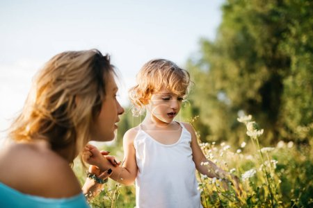 mother and child looking at flowers in green field