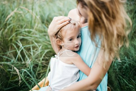Photo for Mother and daughter sitting and hugging in green grass - Royalty Free Image