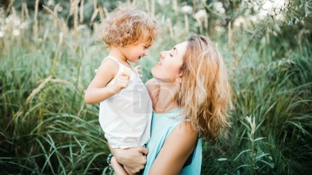 Photo for Side view of smiling mother holding adorable child in green grass - Royalty Free Image