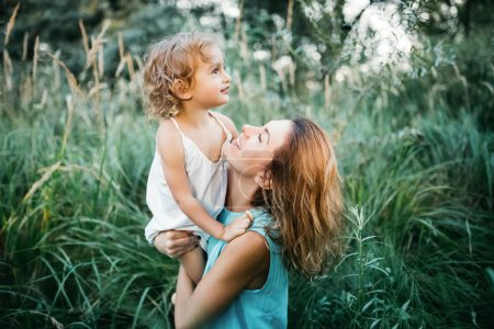 Photo for Side view of happy mother holding adorable child in green grass - Royalty Free Image