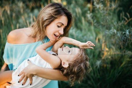 Foto de Feliz madre divirtiéndose con la hija en el campo - Imagen libre de derechos