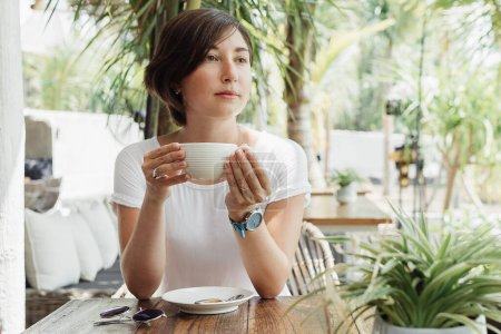 Photo for Woman drinking cappuccino at cafe outdoors excellent coffee - Royalty Free Image