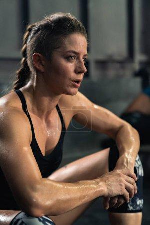 Photo pour La fille après une séance d'entraînement crossfit fatigué assis. repos après l'entraînement. athlète professionnel dans la salle de gym - image libre de droit