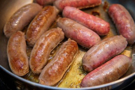 Cooking fried spicy Italian sausage in kitchen pan...