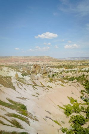 elevated view of slopes in valley and mountains under cloudy blue sky, Cappadocia, Turkey