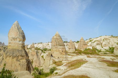 scenic view of stone formations in valley under blue sky, Cappadocia, Turkey