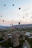 front view of hot air balloons flying over stone formations, Cappadocia, Turkey