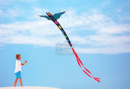 Photo for Happy kid, boy flying a kite in the summer sky - Royalty Free Image