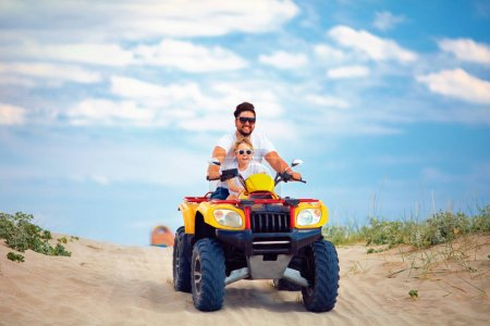 Photo pour Famille heureuse, père et fils à vélo quad atv à la plage de sable - image libre de droit