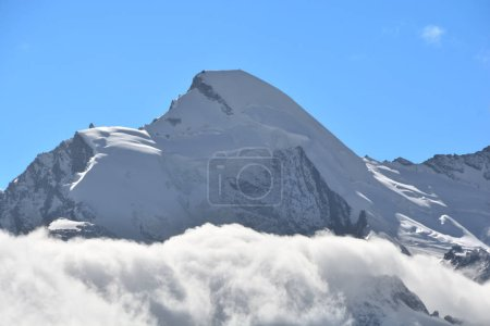 Photo for The summit of the Allalinhorn rising above the clouds. to the right the revolving glacier restaurant of Mittel Allalin above Saas Fee in the Swiss Alps - Royalty Free Image