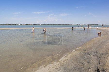 Photo pour Evpatoria, en Crimée - 5 juillet 2018: Personnes laver boue thérapeutique dans lac Lucie à la périphérie de la ville d'Evpatoria du resort, Crimée - image libre de droit