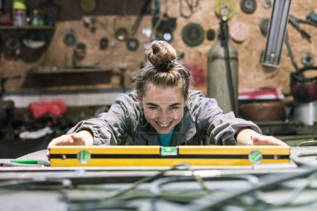 Photo for Happy young woman working in a workshop - Royalty Free Image