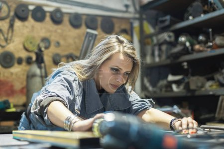 Photo for Young woman working in workshop - Royalty Free Image