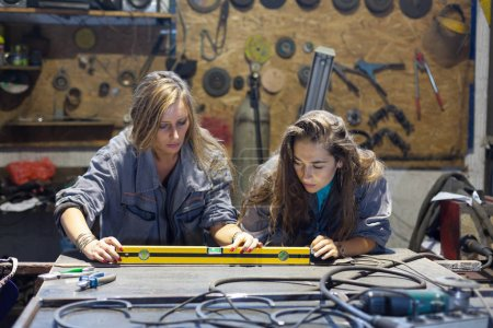 Photo for Young women working in a mechanic shop - Royalty Free Image