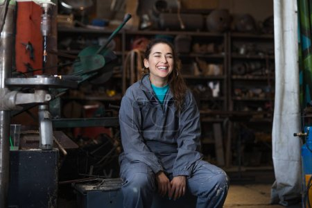 Photo for Young woman mechanic in a workshop - Royalty Free Image