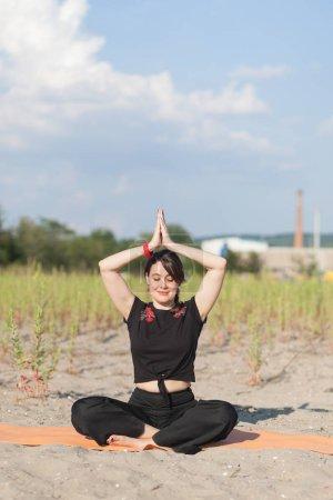 Photo pour Jeune femme faisant du yoga en plein air - image libre de droit
