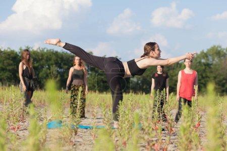 Foto de Profesor de yoga y estudiantes haciendo yoga al aire libre - Imagen libre de derechos