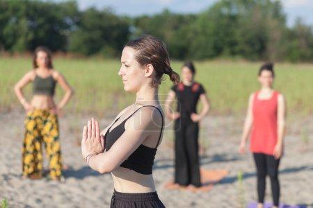 Photo pour Professeur de yoga et étudiants faisant du yoga en plein air - image libre de droit