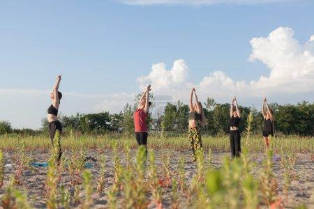 Foto de Yoga en grupo realizando saludos al sol en ambiente al aire libre - Imagen libre de derechos