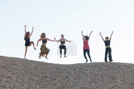 Photo for Five girlfriends jumping with joy on pebble hill - Royalty Free Image