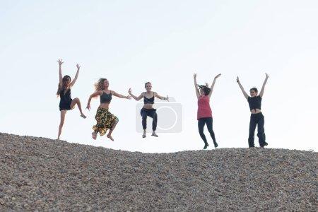 Photo pour Cinq copines sautant de joie sur la colline de galets - image libre de droit