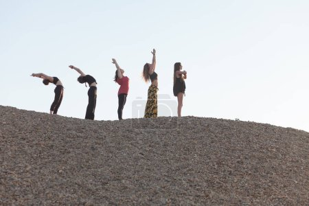 Photo for Segment of yoga sun salutation cycle performed by five women - Royalty Free Image