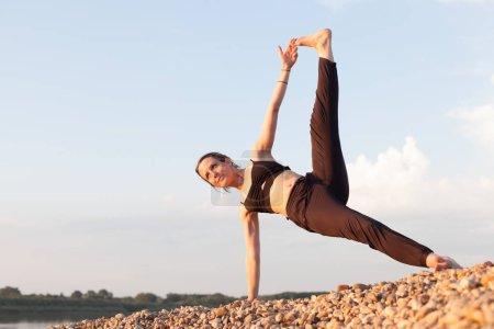 Photo pour Jeune femme pratiquant le yoga en plein air - image libre de droit