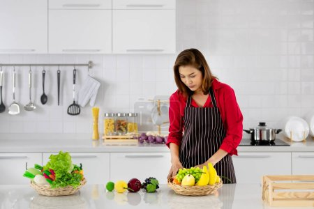 Beautiful Asian woman in red shirt and black  apron standking and arranging fake fruits and vegetables for decoration in white clean kitchen.