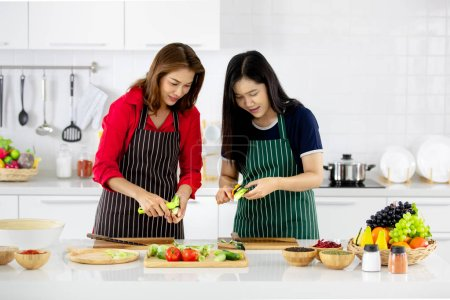 Beautiful Asian woman in red shirt and black  apron teaching her daughter how to prepare vegetables for cooking in white clean modern kitchen.