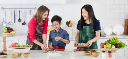Beautiful Asian woman in red shirt and black  apron teaching her daughter and son how to prepare vegetables for cooking in white clean modern kitchen.