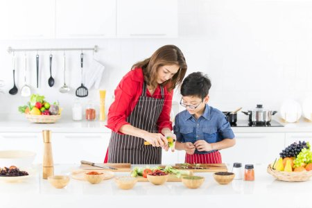 Asian family mom in red shirt and black  apron is teaching her son use  tool to peel fruit and vegetables to prepare food in white clean modern kitchen.