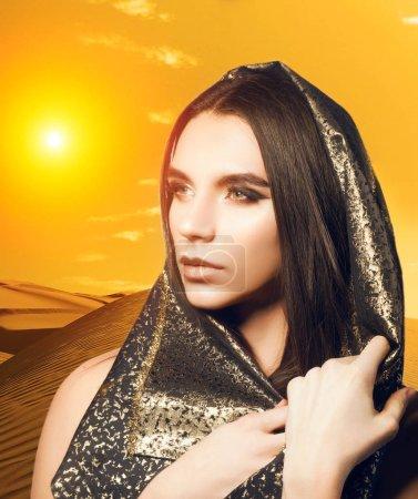 Photo pour Portrait de style arabe de l'androgyne homme féminin en tissu Arabian avec soirée make up et coiffure longue brillante - image libre de droit