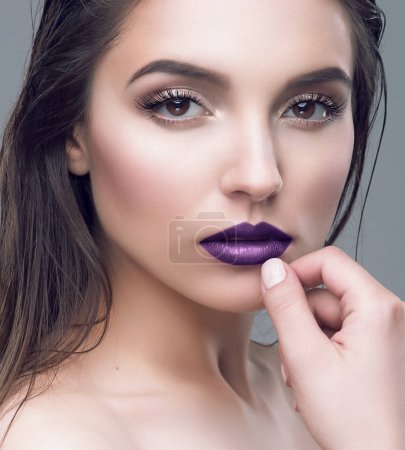 Studio portrait of beautiful young woman with purple lips and wet brown hair