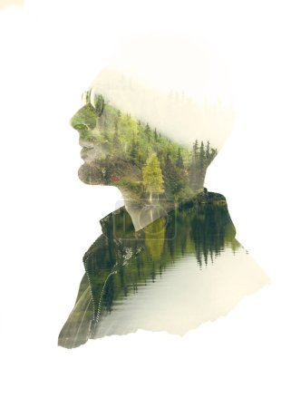 Double exposure silhouette of thoughtful man with green forest landscape in water reflection.
