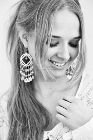 smiling young woman with long blond hair and arabian style earrings. Black and white.