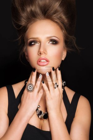 Beautiful woman with hairstyle, bright smokey eyes fashion makeup. Luxurious chic jewelry, vintage rings