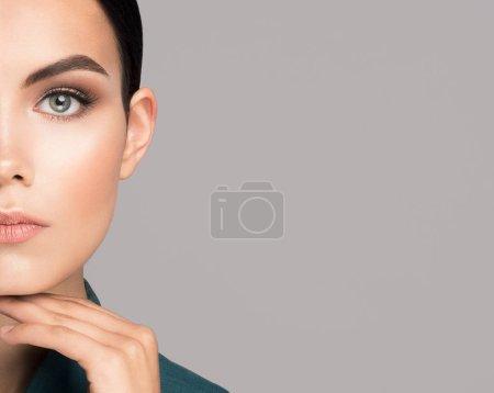 Photo pour Gros plan sur la culture de la jeune femme caucasienne brune avec une peau fraîche regardant devant la caméra avec une main sur un menton. Isolé sur fond gris avec espace de copie pour le texte. Cosmétiques aspect commercial - image libre de droit