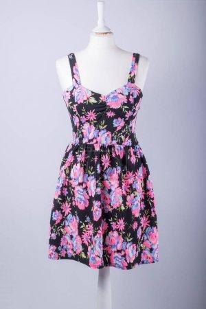 Photo pour Un mannequin tailleur vêtu d'une robe florale noire et rose - image libre de droit