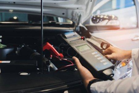 Photo pour Inspection de l'homme tenant testeur de capacité de batterie Voltmeter.for entretien d'entretien de réparation industrielle à moteur. - image libre de droit