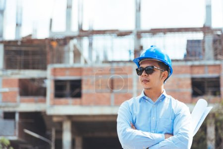 Civil engineer with blue safety helmet and sunglasses at construction site.