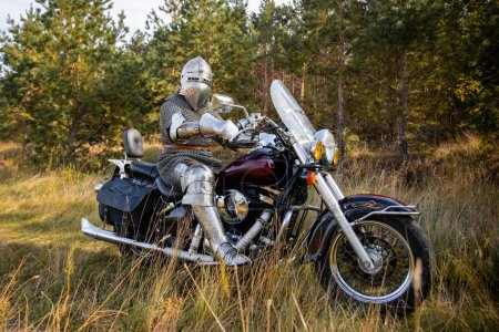 Photo for A medieval knight in chain mail and a helmet sits on a motorcycle. A trip through the woods. - Royalty Free Image