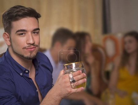 Young man drink beer in a vintage athmosphere pub restaurant bar and friend on blured background