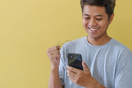 Photo pour A man who uses a cell phone and smiles happily stands in front of the yellow scene. - image libre de droit