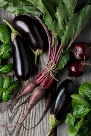 Photo pour Vegetables on the black background. Organic foods and fresh vegetables. Beets, buklazhany, onions and herbs basil. Top view - image libre de droit